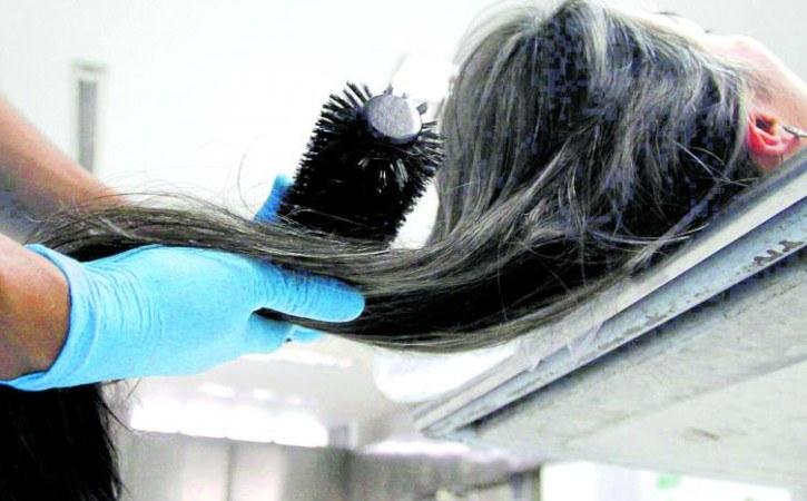 peinando a un difunto durante la preparación tanatológica