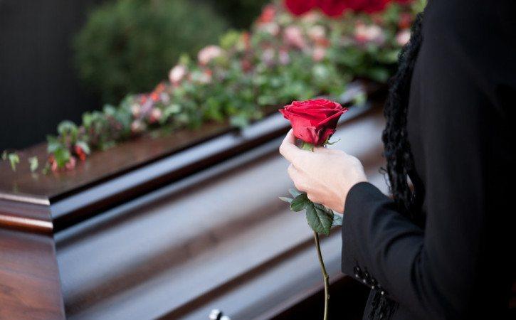 persona con una rosa roja en funeral